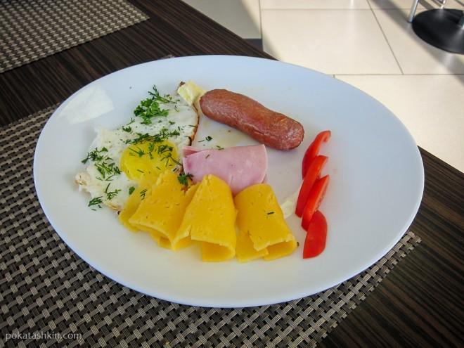 Обжаренная сосиска, яичница, сыр, ветчина, кусочек масла и немного овощей