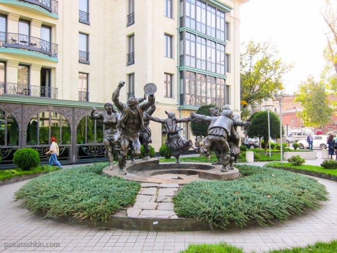 Скульптура с бегущими по кругу людьми